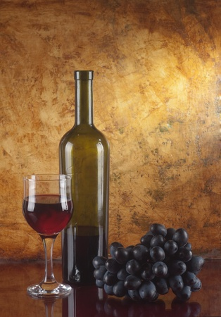 still life of wine: glass of red wine and bottle