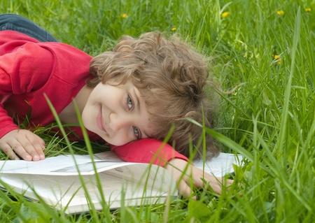 Beautiful little girl reads book, lying on green lawn. Stock Photo - 9507000