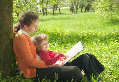 Moeder en dochter lezen van het boek in een park.Onderwijs concept  Stockfoto