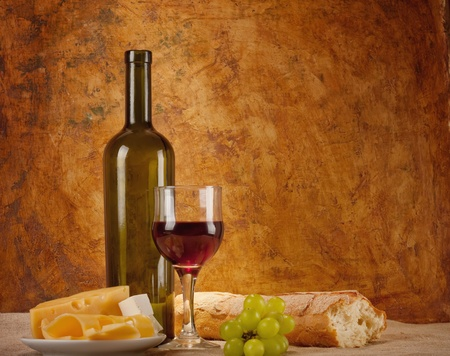 Red wine, assorted cheeses, bread and grapes in a still life setup.  photo