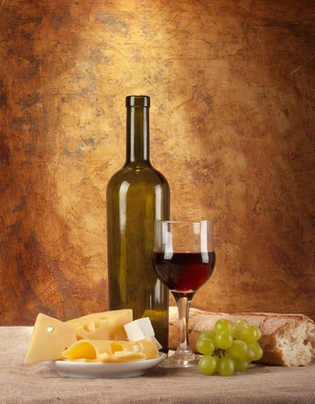 Red wine, assorted cheeses, bread and grapes in a still life setup.  Stock Photo