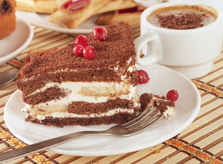 Close-up of white cup of coffee and chocolate cake  photo