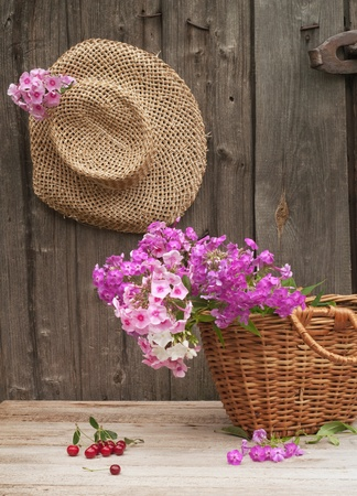 basket of flowers and a straw hat against the background of the old wooden walls photo
