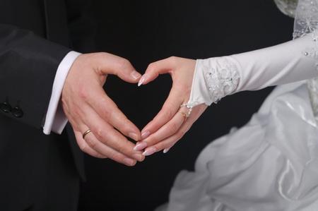 Newlyweds make heart fingers.  photo