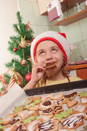 girl in santa hat eating Christmas cookies photo