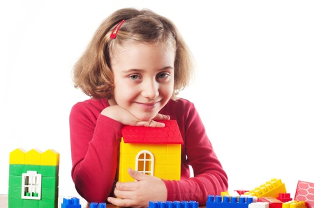Cute little girl is constructing a house using building blocks  Stock Photo - 12537031