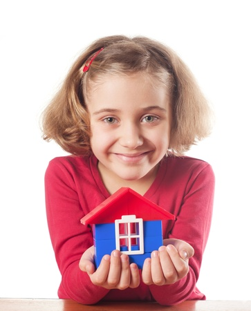 Cute little girl is constructing a house using building blocks  photo