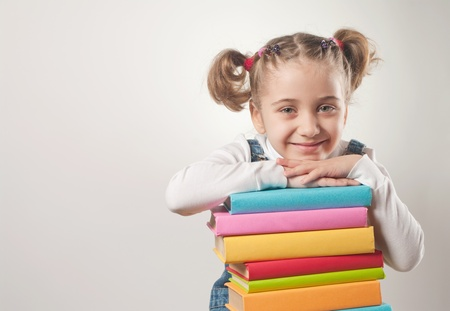 able: Little girl holding pile of books