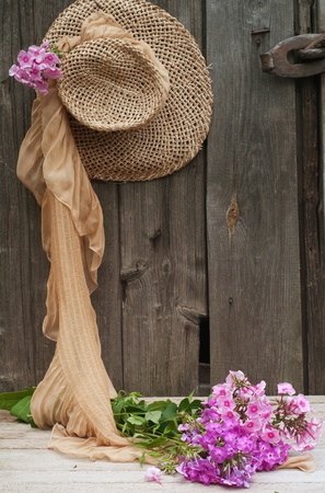 flowers and a straw hat against the background of the old wooden walls  photo