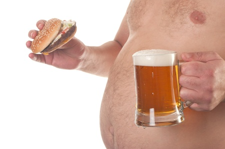 unhealthy lifestyle: fat man with a hamburger and beer in his hand  Stock Photo