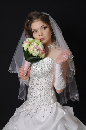 Beautiful bride with wedding bouquet on a dark background photo