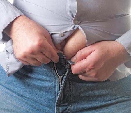 obesidad: El sobrepeso del hombre tratando de sujetar la ropa demasiado peque�as aisladas sobre fondo blanco Foto de archivo