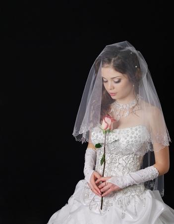 Estudio de retrato de una joven novia con un vestido de novia blanco con velo, que sostiene las flores.