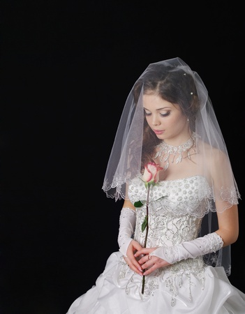 long gown: Studio portrait of a young bride wearing a white wedding dress with veil, holding flowers.