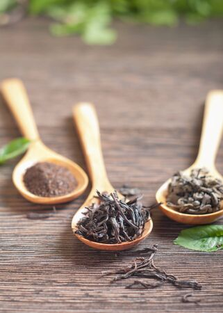 Different kinds of green and black dry tea in  spoon against a wooden table photo