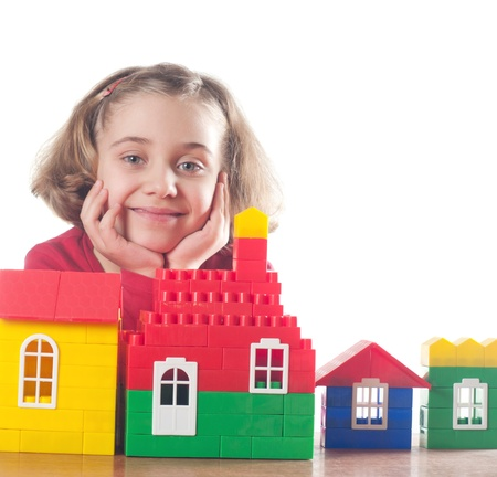 Cute little girl is constructing a house using building blocks Stock Photo - 13338355