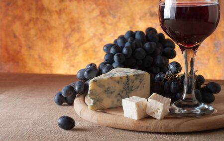Red wine, assorted cheeses and grapes in a still life setup.  photo