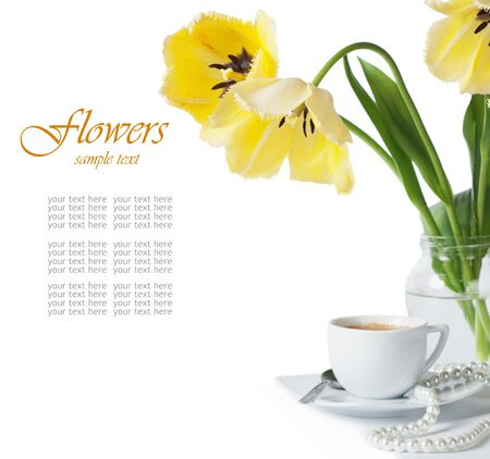 beautiful yellow tulips and a cup of coffee on a white background photo