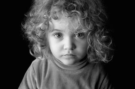 petite fille triste: Portrait noir et blanc d'une belle petite fille Banque d'images