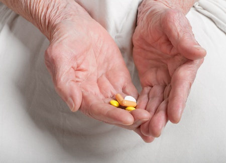 pill on the hands of old woman  photo