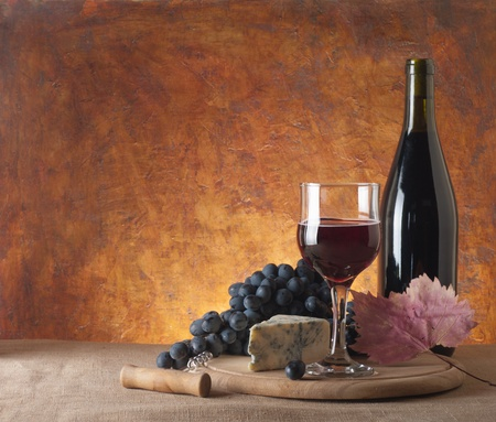 winetasting: Red wine, assorted cheeses, bread and grapes in a still life setup.  Stock Photo