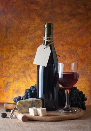 Red wine, assorted cheeses, bread and grapes in a still life setup. Stock Photo - 13356933