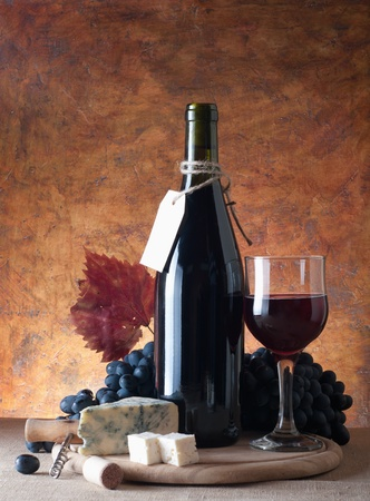 Red wine, assorted cheeses, and grapes in a still life setup.  photo
