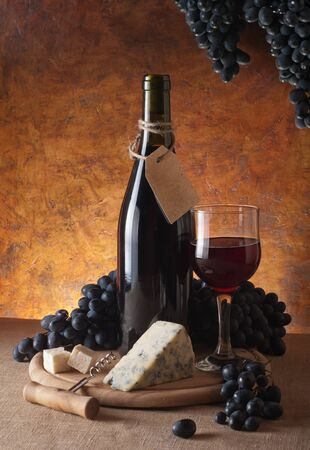 Red wine, assorted cheeses, and grapes in a still life setup.  Stock Photo - 13356930