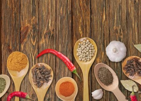 culinaire: �pices dans les cuill�res sur fond de bois
