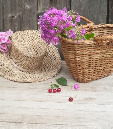 straw hat: cesto di fiori e un cappello di paglia sullo sfondo delle antiche mura di legno Archivio Fotografico
