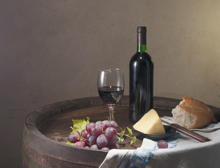 cheese platter: Red wine, assorted cheeses, bread and grapes in a still life setup