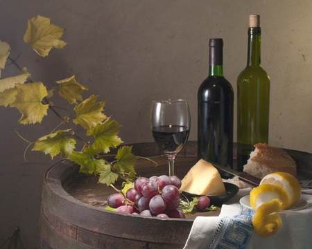 Red wine, assorted cheeses, bread and grapes in a still life setup   photo