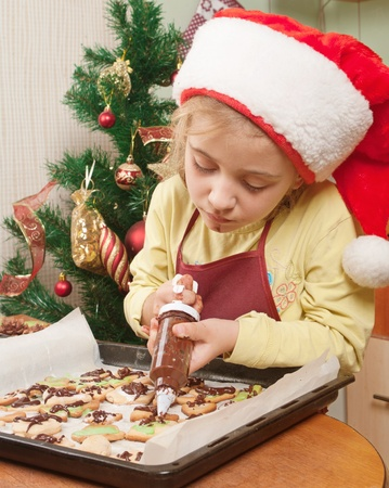 Little girl decorating the christmas cookies  photo