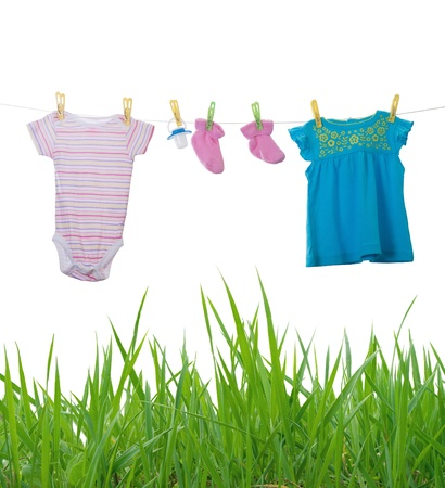 clean clothes: Baby clothes drying on a rope isolated on white background