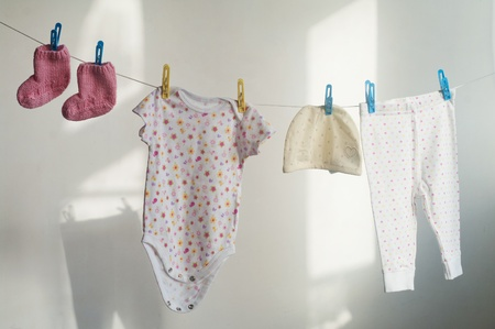 dirty clothes: Baby laundry hanging on the rope