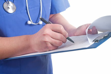 Hand of doctor with pen writing on prescription blank photo