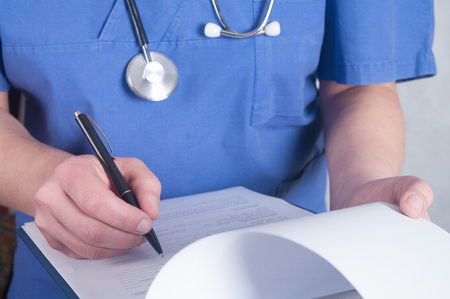 doctor writing: Hand of doctor with pen writing on prescription blank Stock Photo