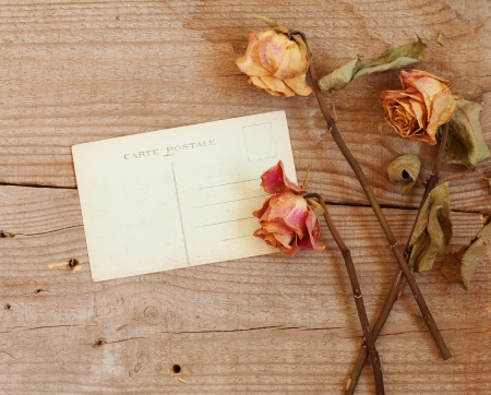 postcard and a dry rose on wooden background photo