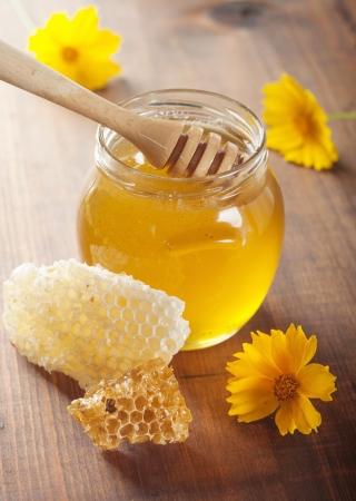 jar of honey and stick on the wooden table photo