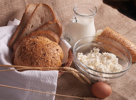 dairy product: jug with milk, eggs, cottage cheese and bread on burlap background