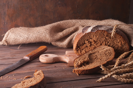 wheat and bread on a wooden table photo