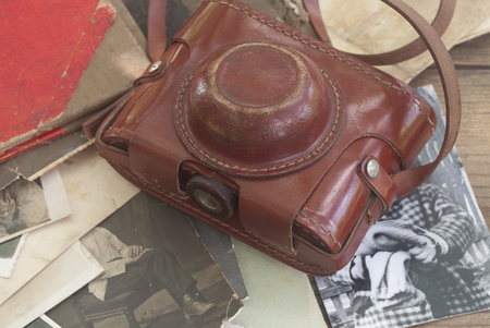 vintage camera and album with old photos on wooden table photo