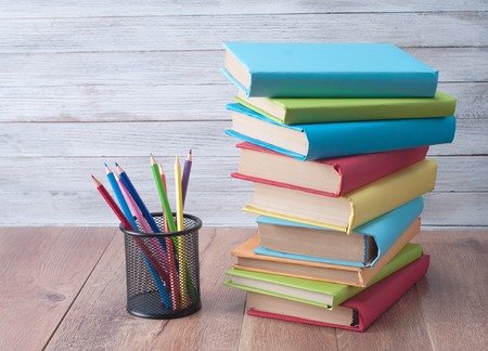 Books and pencils on a wooden background. photo