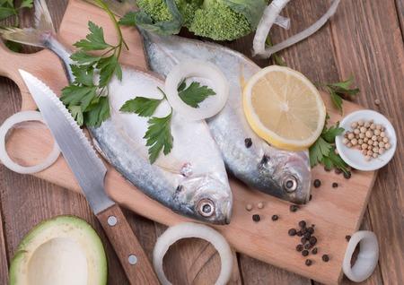 Delicious fresh sea bream fish on wooden kitchen board photo