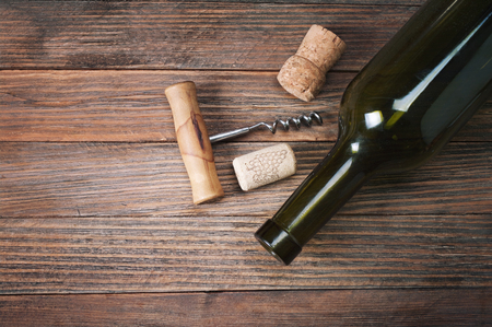 Bottle of wine and corkscrew on wooden table photo