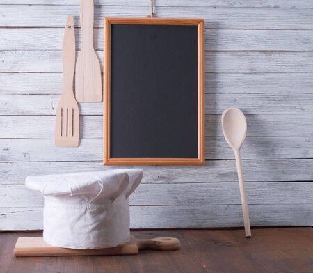 Blackboard on wooden surface and serving spoons photo
