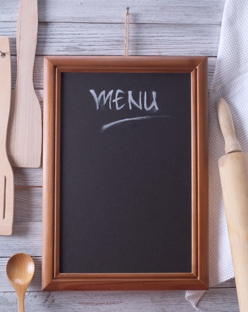 Blackboard on wooden surface and serving spoons