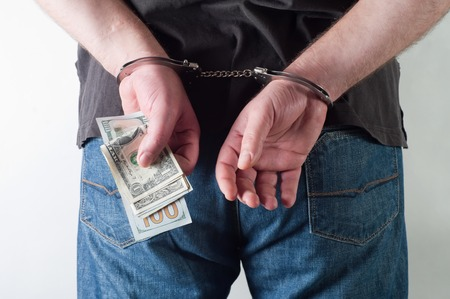 man in handcuffs is holding dollars photo