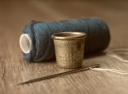 thimble and needles for sewing close-up on a background thread spools. macro Stock Photo