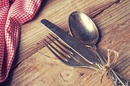 grunge flatware: old cutlery on wooden table